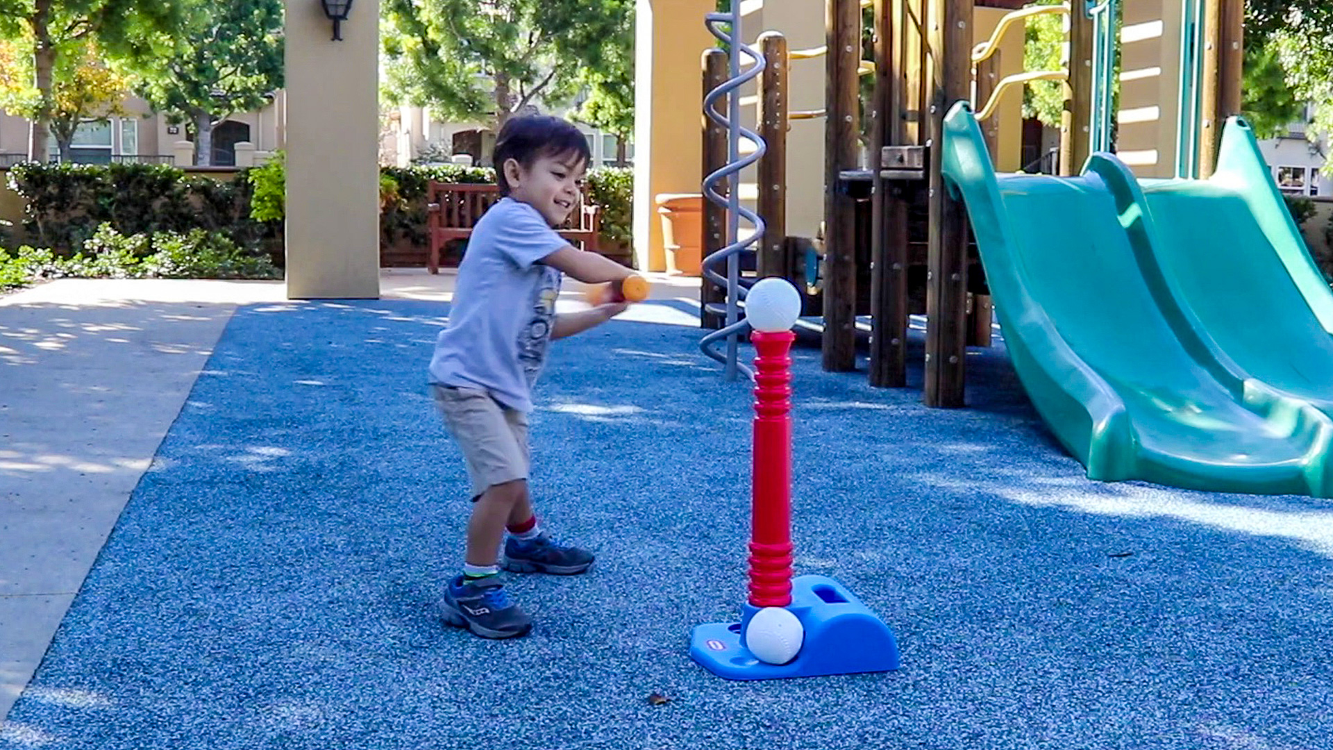 3 year old boy swinging a bat with the T-ball set