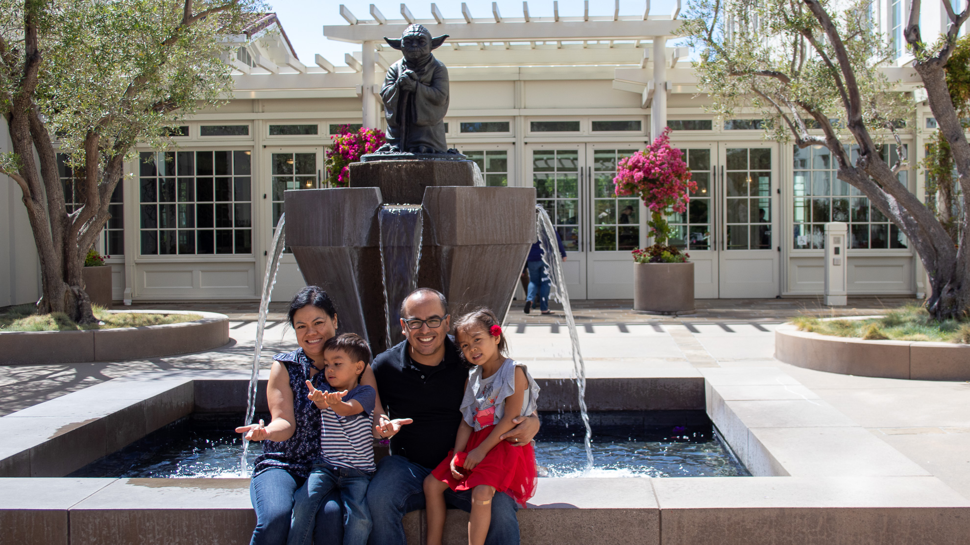 Oscar Gonzalez and family posing next to the Yoda water fountain.